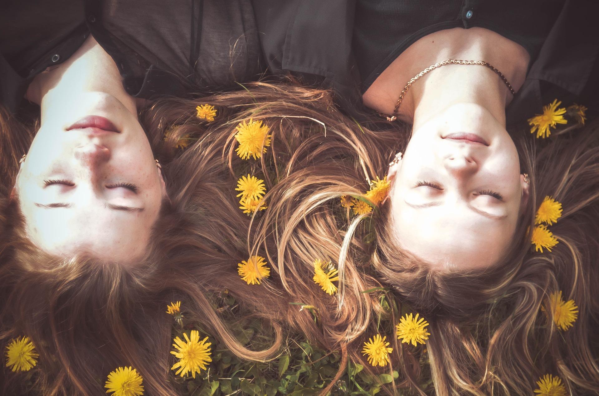 Duas meninas deitadas no chão com flores em volta da cabeça